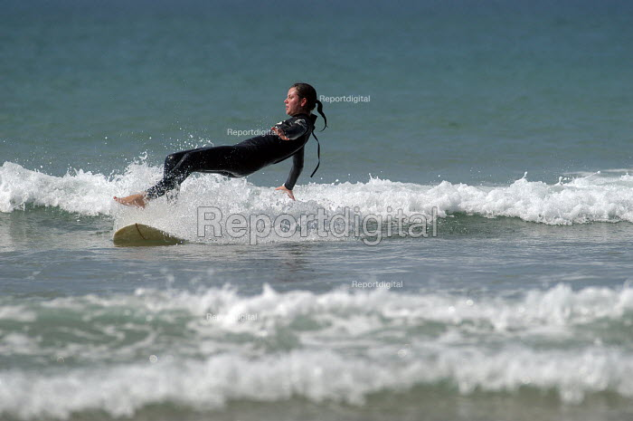 A learner surfer falls off her board whilst learning to surf , Freshwater west, Pembrokeshire. - Paul Box - 2004-03-01