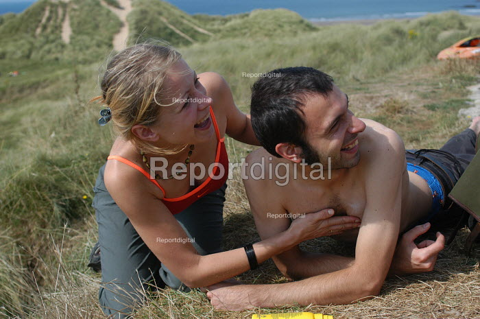 A couple putting on suncream on a hot day, Freshwater west, Pembrokeshire. - Paul Box - 2003-08-20