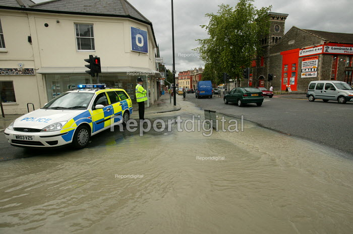 Police officer attends a bust water main in Bristol, the road has been closed. - Paul Box - 2004-06-10