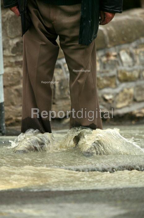 Flood water runs down the pavement. A man gets wet trousers. - Paul Box - 2004-06-10