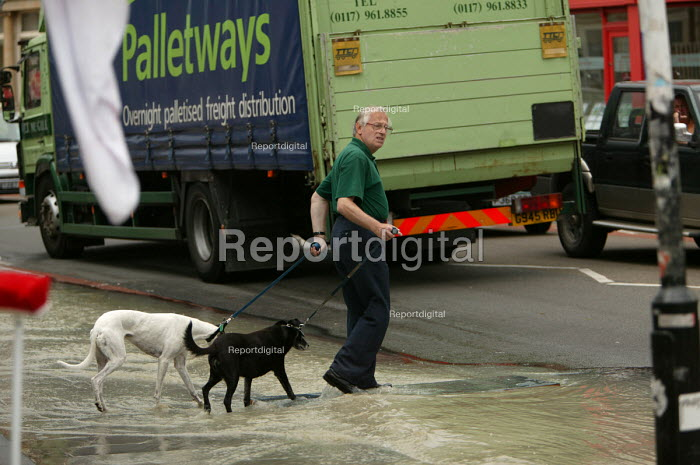 Flood water from a bust water main in Bristol runs down the pavement. A man crosses with his dogs. - Paul Box - 2004-06-10