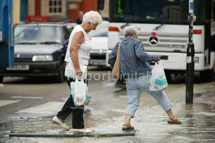 Flood water from a bust water main in Bristol runs down the street. A couple of elderly ladies cross the stream on a plank - Paul Box - 2004-06-10