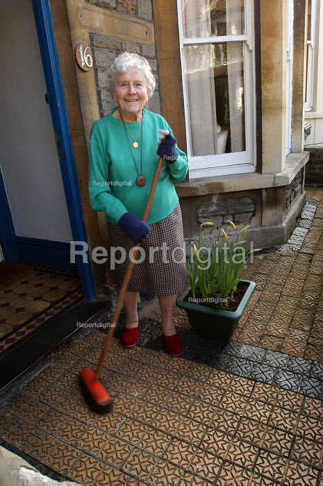 A 90 year old widowed woman sweeps her porch outside her home in Bristol. - Paul Box - 2004-08-02