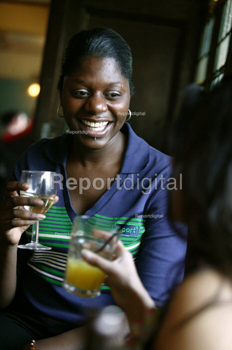 A female student in a pub with a drink, Bristol. - Paul Box - 2004-07-02
