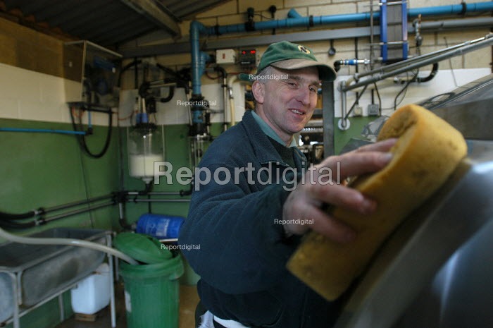 Defra organic farming scheme. A rented dairy farm in gloucestershire. The farmer in the milking shed. - Paul Box - 2004-07-02