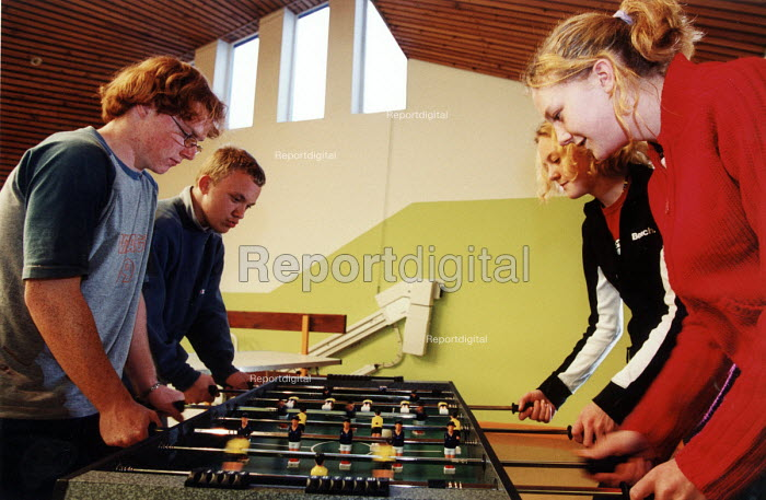 Teenagers at a youth centre playing table football. - Paul Box - 2004-08-02