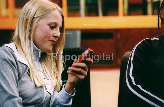 Teenagers at a youth centre, a girl texting on her mobile phone. - Paul Box - 2004-08-02