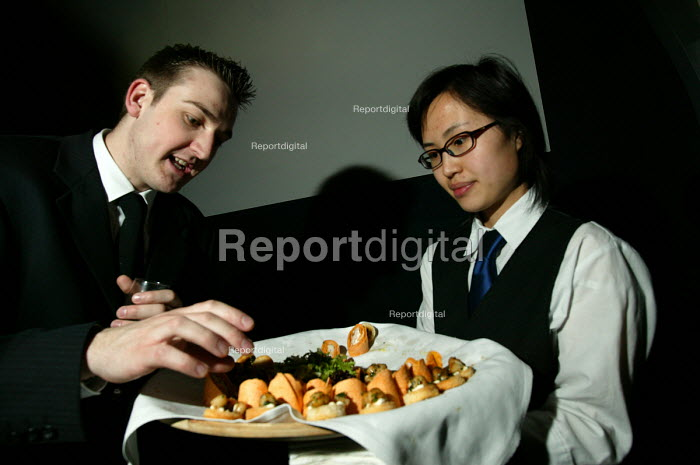 A chinese waitress serves food at a corporate event, Bristol. - Paul Box - 2004-08-02