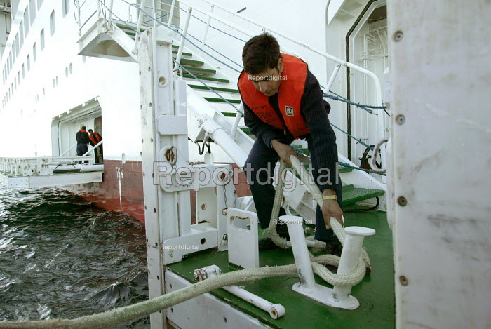 The Aurora cruise ship, a P&O cruise ship. Indonesian workers untie the tender. - Paul Box - 2004-06-02