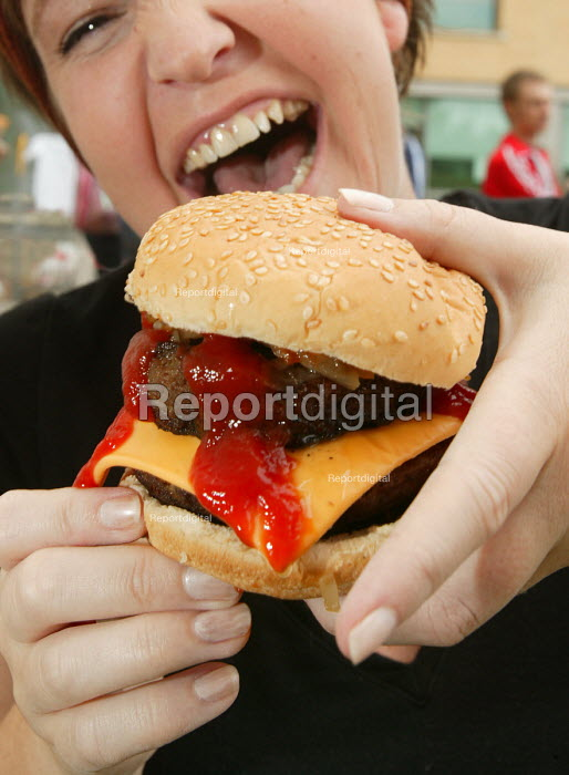 A young woman eating a burger with tomato Ketchup. - Paul Box - 2004-06-02