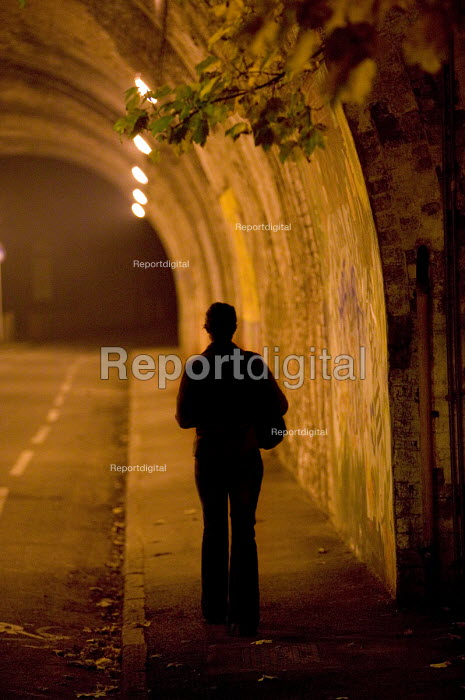 A woman walks through the streets at night down an underpass. - Paul Box - 2005-12-07