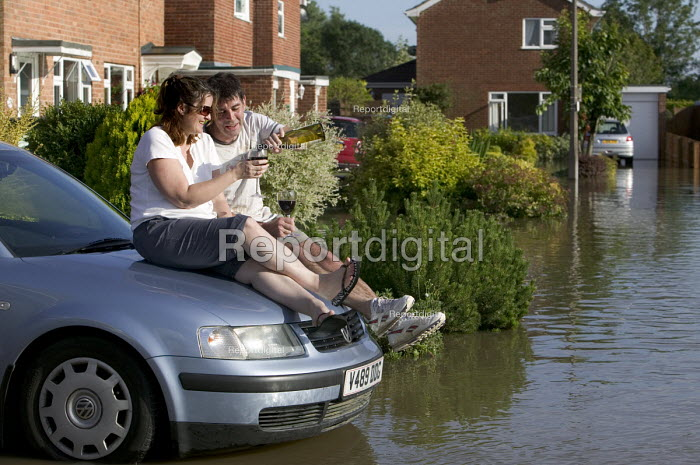 Local residents share a glass of wine as flood water rises... - Paul Box, PB707042.jpg