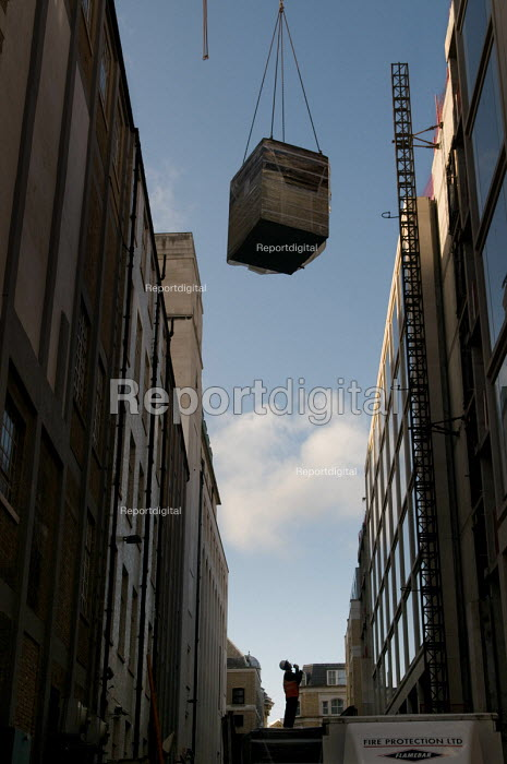 A construction worker watches as a crane lifts a load on a... - Philip Wolmuth, pw080121.jpg