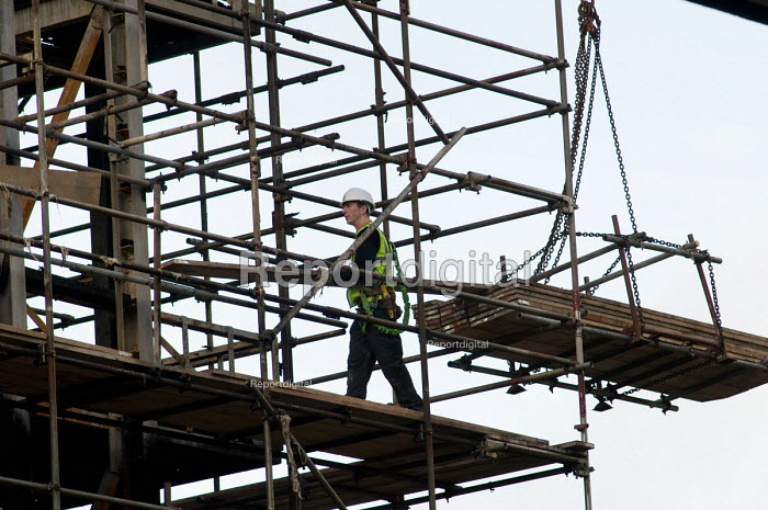 A scaffolder unloads planks lifted by crane on a building... - Philip Wolmuth, pw080138.jpg