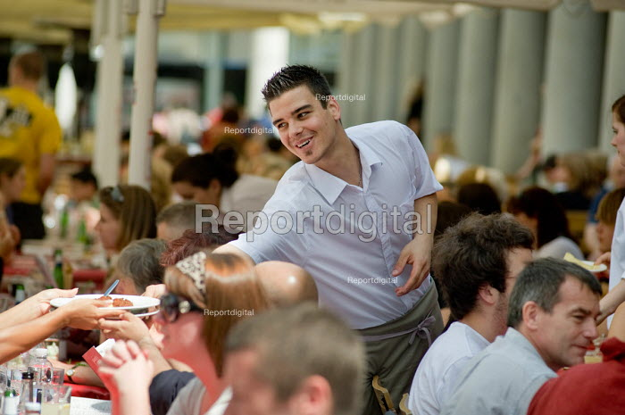 A waiter serves customers at a restaurant and cafe in... - Philip Wolmuth, pw090741.jpg