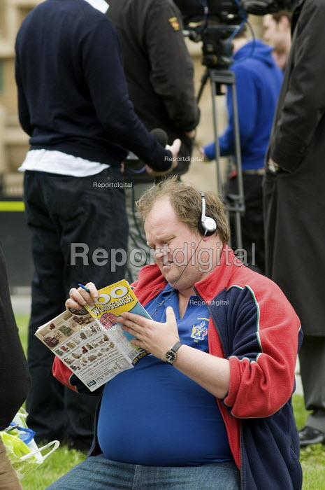 A TV sound technician passes the time reading a wordsearch magazine, Westminster, 2010 General Election. - Philip Wolmuth - 2010-05-11