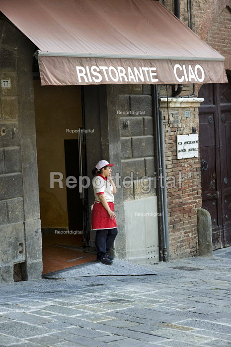 A catering worker talks on a mobile phone outside a restaurant in Siena during a cigarette break. - Philip Wolmuth - 2010-06-06