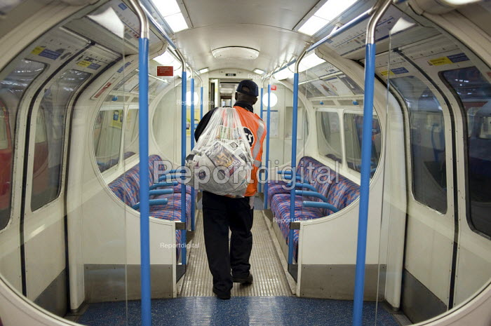 A cleaner collects and bags discarded newspapers from a carriage at London Underground's Northumberland Park Depot, which services the 42 tube trains on the Victoria line. - Philip Wolmuth - 2009-12-03