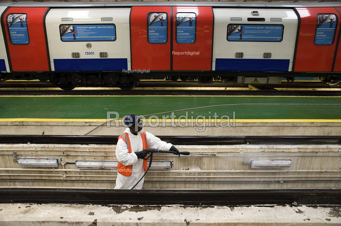 A cleaner spraying off accumulated grease from the engineering pit at London Underground's Northumberland Park Depot, which services the 42 tube trains on the Victoria line. - Philip Wolmuth - 2009-12-03