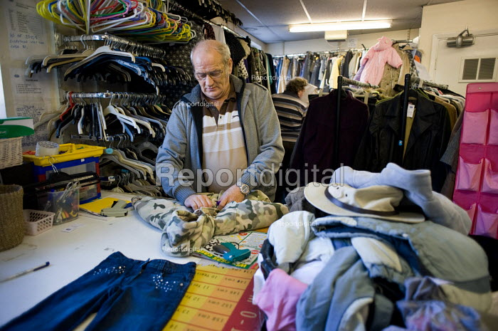 A Job Seekers Allowance claimant on a compulsory four week unpaid work placement in an RSPCA charity shop in Middleton, Rochdale, part of a Mandatory Work Related Activity welfare-to-work programme. - Philip Wolmuth - 2010-10-07
