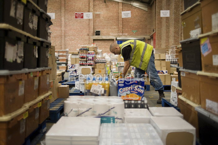 An ex-claimant of Job Seekers Allowance working in a warehouse on Stakehill Industrial Estate, Oldham, following a compulsory four week unpaid work placement, part of a Mandatory Work Related Activity welfare-to-work programme. - Philip Wolmuth - 2010-10-07