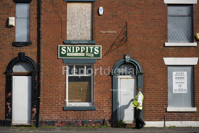 A security guard patrols houses in Derker, Oldham, checking a door is locked, the houses are scheduled for demolition as part of the Housing Market Renewal programme. - Philip Wolmuth - 2010-10-08