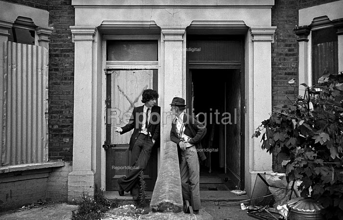 Squatter and a workman talking on the doorstep of a house in Bravington Road, London 1977 houses being gutted following an eviction. Many neighbouring houses were boarded up and in very poor condition. Bravington, Portnall and Ashmore Road became a Housing Action Area - Philip Wolmuth - 1977-05-05