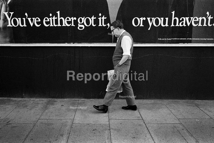 1983: You've either got it, or you haven't. A man walks past an advertising hoarding on the Harrow Road, West London. - Philip Wolmuth - 1983-08-10