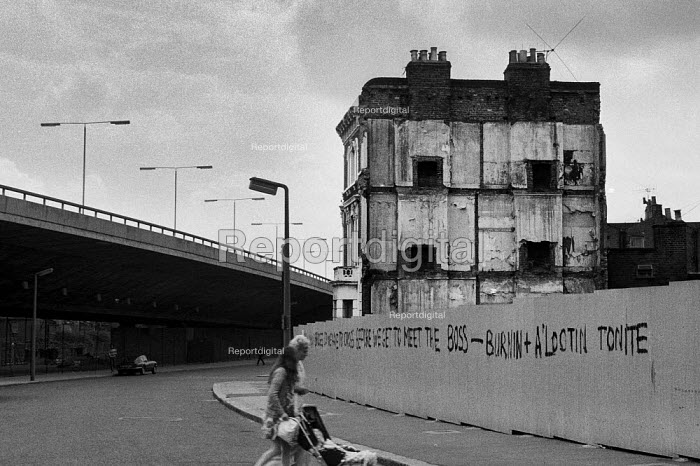 1975: Demolition of houses on Acklam Road, Notting Hill, West London. Graffiti: HOW MANY BRIDGES DO WE NEED TO CROSS BEFORE WE GET TO MEET THE BOSS - BURNIN' and A LOOTIN' TONITE after Bob Marley and The Wailers. - Philip Wolmuth - 1975-03-14