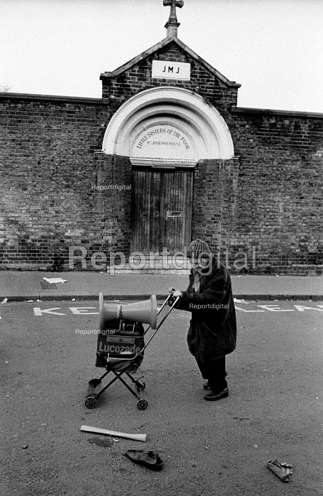 1983: after the market: a man collects cast-offs outside the closed Little Sisters of the Poor Catholic convent and home for the elderly on Portobello Road, Notting Hill, London. - Philip Wolmuth - 1983-03-12