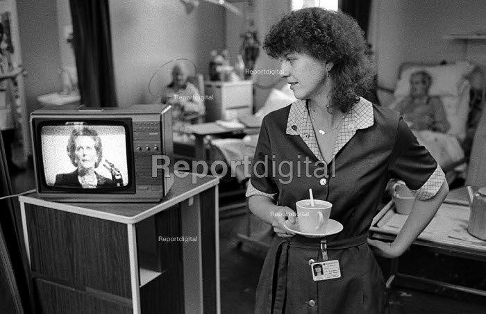 1986: a domestic worker at St Charles Hospital, Notting Hill, newly contracted out to cleaning company Mediclean, watches a televised speech by Prime Minister Margaret Thatcher. - Philip Wolmuth - 1986-10-10