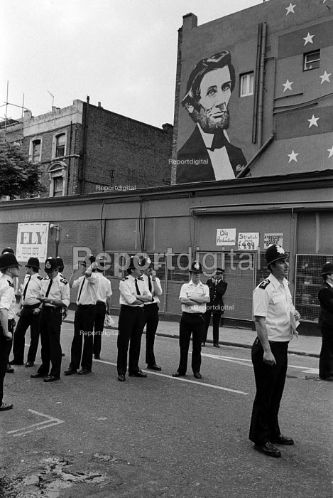 1981 police stand guard on the corner of Westbourne Park Road and Portobello Road beneath a mural of anti slavery American president Abraham Lincoln during the Notting Hill Carnival - Philip Wolmuth - 1981-08-31