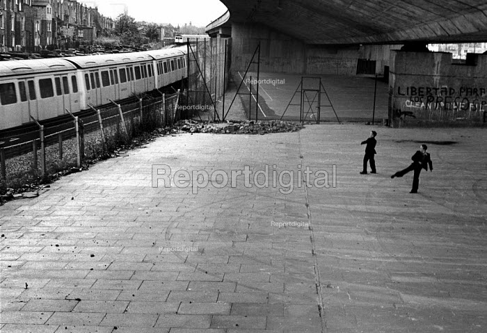 1977: Boys throwing stones at a London Underground train as it passes by the Westway flyover, West London. - Philip Wolmuth - 1977-05-16