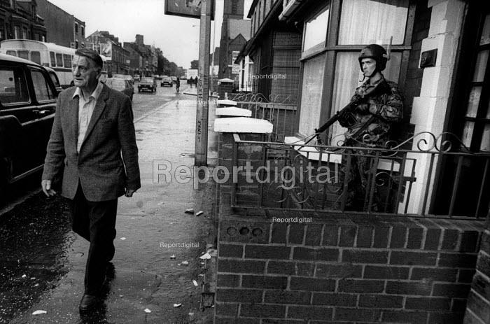 Man walks past a British soldier on patrol, Falls Road, Belfast, 1984 - Philip Wolmuth - 1984-07-30