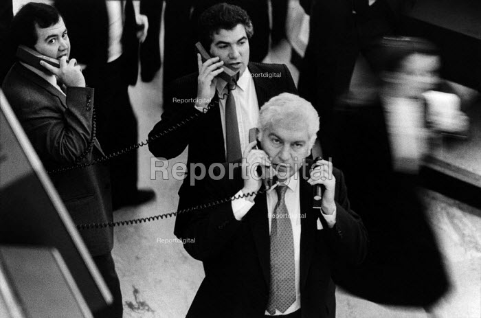 Dealers on the floor of the London Stock Exchange resort to telephones when new technology fails on the day of the Big Bang deregulation of financial services by the government. - Philip Wolmuth - 1986-10-27