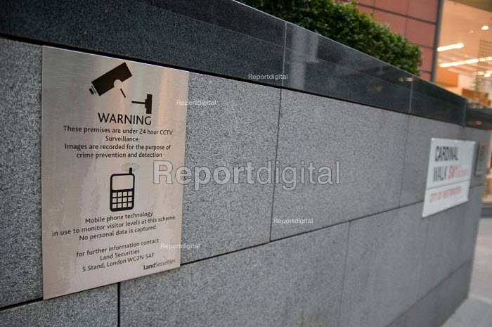 CCTV and mobile phone monitoring warning notice at Cardinal Walk, Victoria, London, an office and retail development owned by the private company Land Securities. Mobile phone technology is in use to monitor visitor levels. - Philip Wolmuth - 2010-12-31