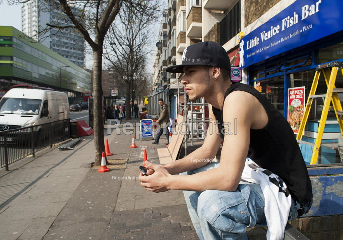 Young man sitting on a wall on the Harrow Road, West London, close to the much wealthier district of Little Venice - Philip Wolmuth - 2011-03-25