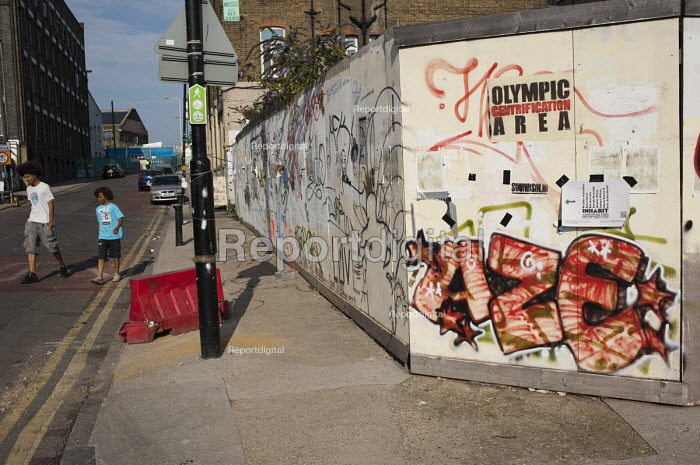 Olympic Gentrification Area. Graffiti on a hoarding in Hackney Wick. A rundown area of warehouses, small industrial units and tenement blocks next to the London 2012 Olympic Park - Philip Wolmuth - 2011-08-01