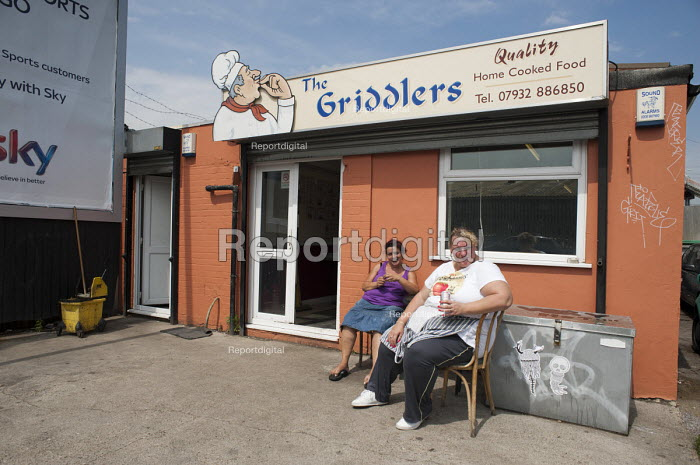 Two women working at The Griddlers cafe in Hackney Wick take a break. It is a rundown area of warehouses and small industrial units next to the London 2012 Olympic Park. - Philip Wolmuth - 2011-08-02
