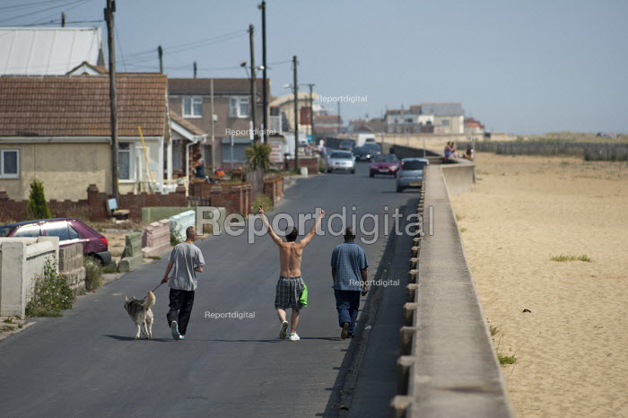 Friends walking along the seafront, Brooklands Estate in Jaywick Sands, Clacton-on-Sea. The estate's small wooden houses - many little bigger than beach huts - were originally built as holiday homes. Brooklands is the most deprived ward in the UK, according to the latest Indices of Multiple Deprivation. - Philip Wolmuth - 2011-08-03