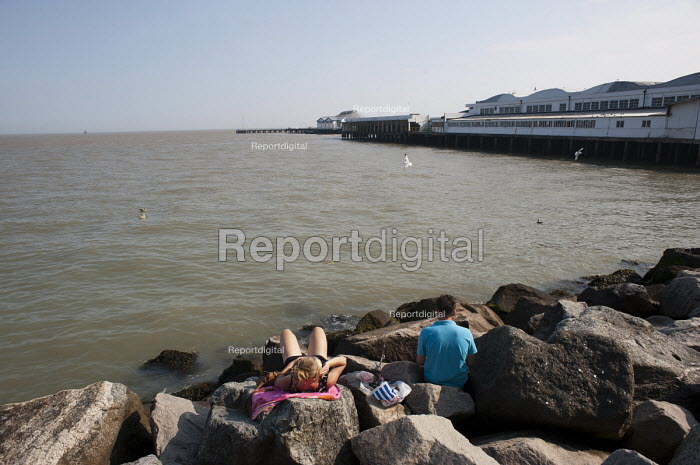 Youth relaxing and sunbathing on the rocks by Clacton pier, Clacton-on-Sea Essex. - Philip Wolmuth - 2011-08-03