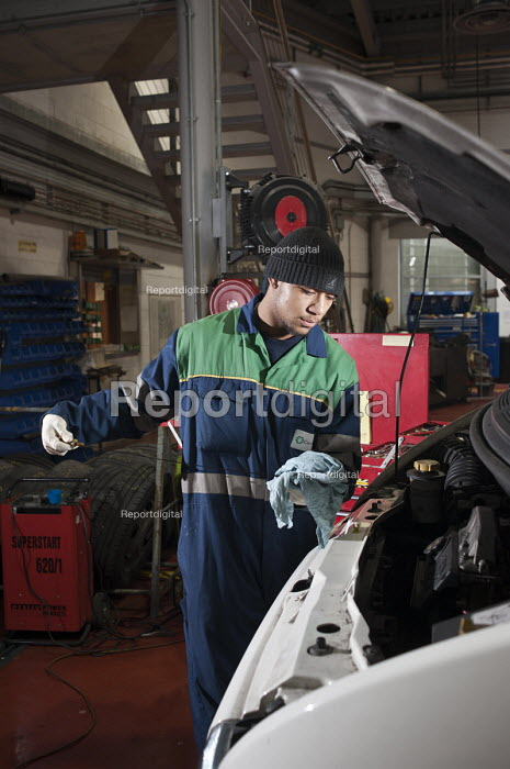 Apprentice vehicle mechanic at Camden Transport Services. Checking the oil level in an engine. - Philip Wolmuth - 2011-03-01