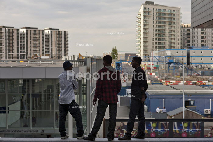Young men look out over the London 2012 Olympic construction site from Westfield Stratford City, the largest urban shopping centre in Europe. - Philip Wolmuth - 2011-09-15