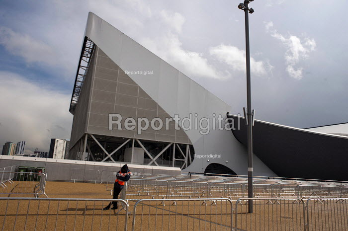 A security guard outside The Aquatics Centre, designed by architect Zaha Hadid, Olympic Park, London. - Philip Wolmuth - 2012-04-19