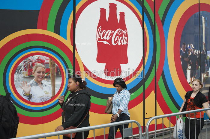 Pedestrians walking past a Coca-Cola advertisement on route to the London 2102 Olympic Park in Stratford. - Philip Wolmuth - 2012-08-08