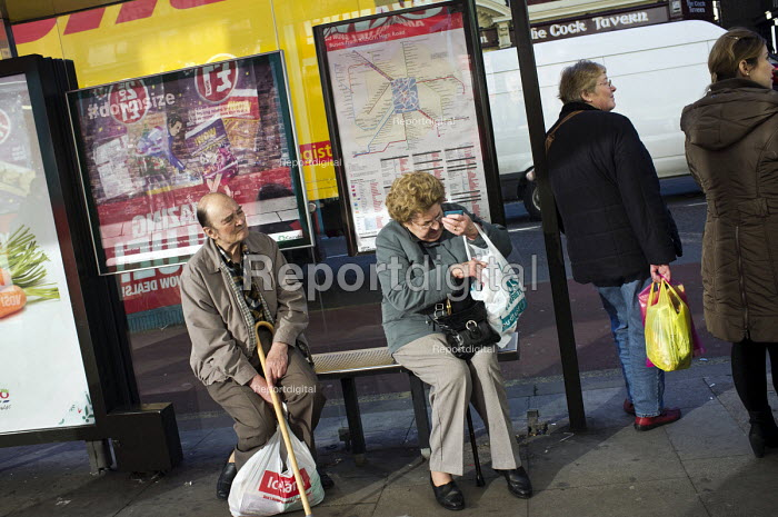 People waiting at a bus stop in Kilburn, London. - Philip Wolmuth - 2012-11-22