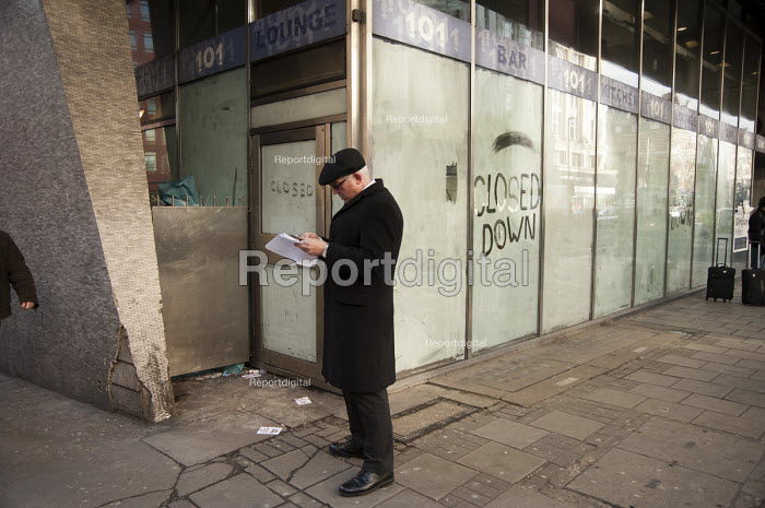 A prospective buyer looking at the particulars of the premises of a closed down, empty, DJ bar and restaurant, 101 Bar, New Oxford Street, central London. - Philip Wolmuth - 2013-01-17