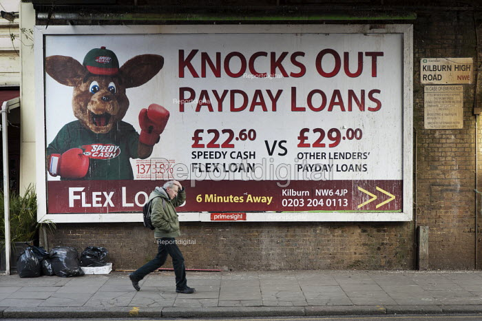 A pedestrian walks past an advertisement for loans at an interest rate of 1373% APR in Kilburn, London. - Philip Wolmuth - 2013-02-28