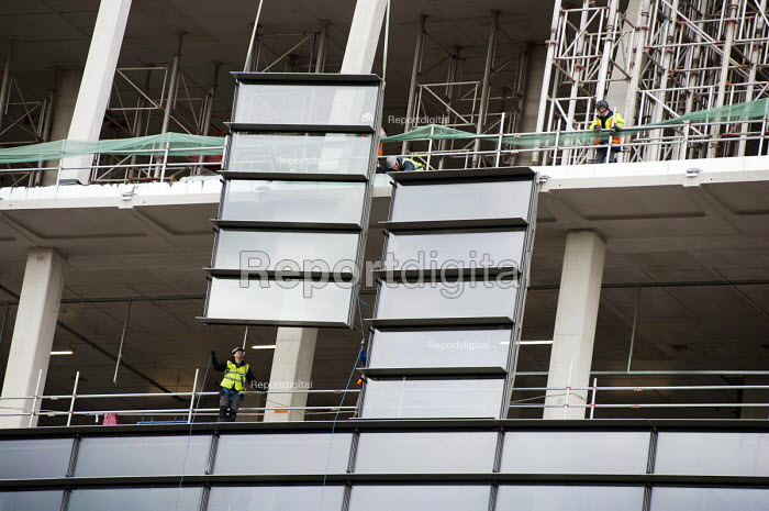 A steel and glass panel is lowered into place by a crane on the Francis Crick Institute, Kings Cross. - Philip Wolmuth - 2013-05-16