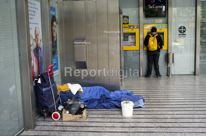 A homeless man sleeps in the entrance to a bank in Granada, Spain. - Philip Wolmuth - 2013-05-18
